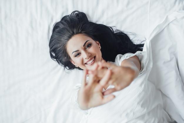 Młoda piękna brunetka szczęśliwa dziewczyna leży w łóżku, budząc się rano i pocąc się. widok z góry.