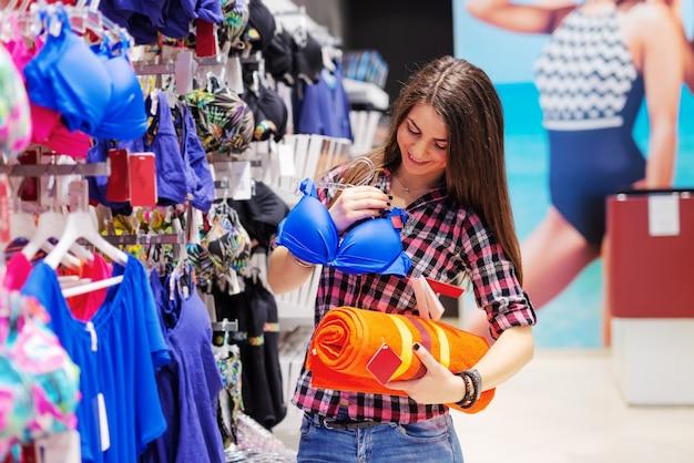 Młoda piękna brunetka ubrana dorywczo przygotowuje się do wakacji. w jednej ręce trzyma bikini, w drugiej ręcznik.