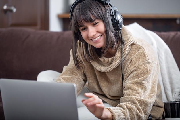 Młoda piękna brunetka uśmiechając się w przytulnym swetrze i patrząc na ekran laptopa. koncepcja szkolenia online, pracy zdalnej, komunikacji wideo.
