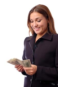 Młoda piękna brunetka w ciemnym garniturze liczy dolary
