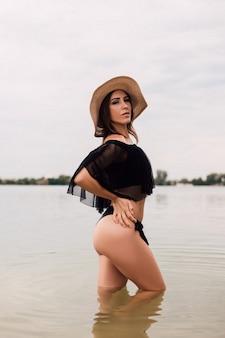 Młoda piękna brunetka w słomkowym kapeluszu stoi w wodzie w naturze