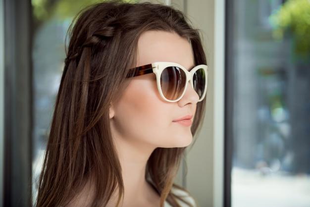 Młoda piękna brunetka z ufnym wyrażeniem, próbuje na eleganckich okularach przeciwsłonecznych podczas gdy robiący zakupy w okulisty sklepie