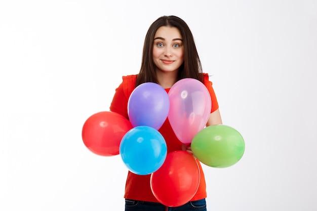 Młoda piękna brunetki dziewczyna ubierał w czerwieni trzyma kolorowych baloons ono uśmiecha się nad biel ścianą