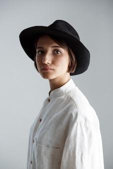 Młoda piękna brunetki dziewczyna w czarnym kapeluszu nad biel ścianą