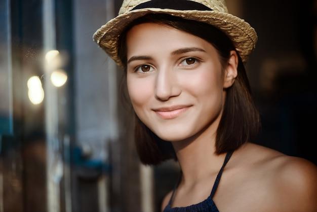 Młoda piękna brunetki dziewczyna w kapeluszowy ono uśmiecha się.