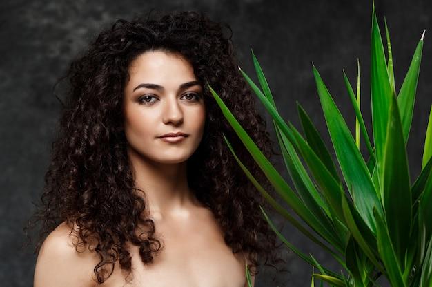 Młoda piękna brunetki dziewczyna w tropikalnych roślinach nad szarości ścianą