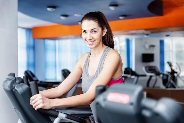 Młoda piękna brunetki kobieta przy gym w cardio strefie.