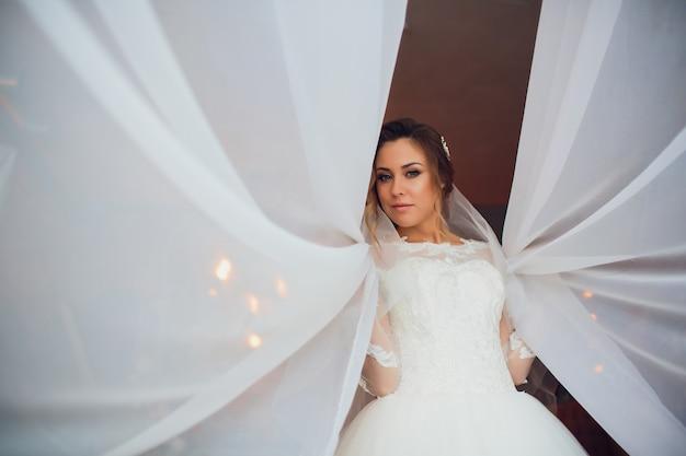 Młoda piękna brunetki kobieta w ślubnej sukni.