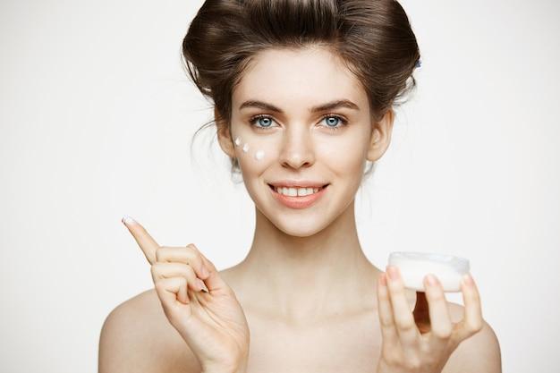 Młoda piękna brunetki kobieta w włosianych curlers uśmiecha się kremową twarz. zabieg na twarz. uroda zdrowie i kosmetologia.