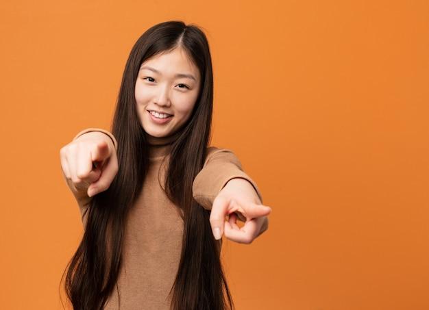 Młoda piękna chinka wesoły uśmiecha się, wskazując na przód.