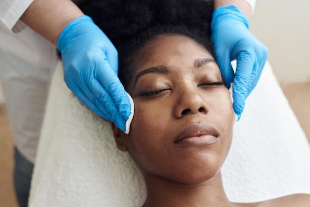 Młoda piękna ciemnowłosa kobieta leży w gabinecie kosmetyczki i wykonuje peeling twarzy