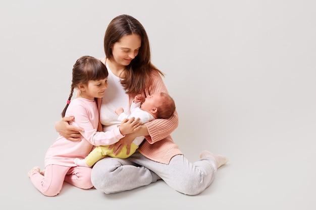 Młoda piękna ciemnowłosa mama z 5-letnią córką i noworodkiem ubrana w codzienne ubrania, relaksująca i bawiąca się razem