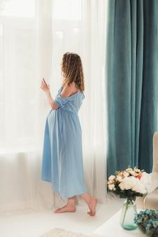 Młoda piękna ciężarna dziewczyna stoi przy oknie w niebieskiej sukience boso z rozpuszczonymi włosami w białym pokoju