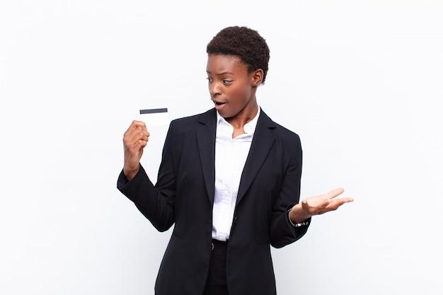Młoda piękna czarna kobieta czuje się bardzo zszokowana i zaskoczona, trzymając kartę kredytową