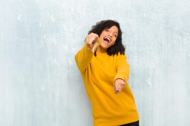 Młoda piękna czarna kobieta czuje się szczęśliwa i pewna, wskazując obiema rękami i śmiejąc się, wybierając ciebie