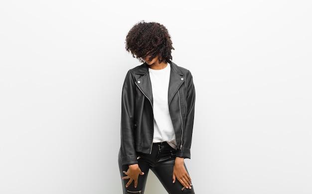 Młoda piękna czarna kobieta tańczy w skórzanej kurtce na białej ścianie