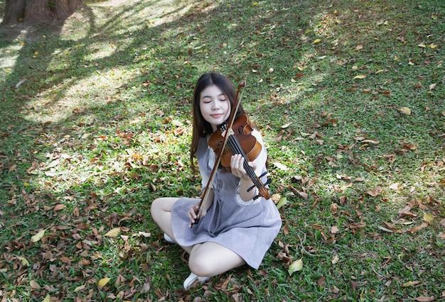 Młoda piękna dama grająca na skrzypcach w parku. czas relaksu, z radosnym uczuciem, odbicie światła słonecznego świeci wokół zielonej trawy parter