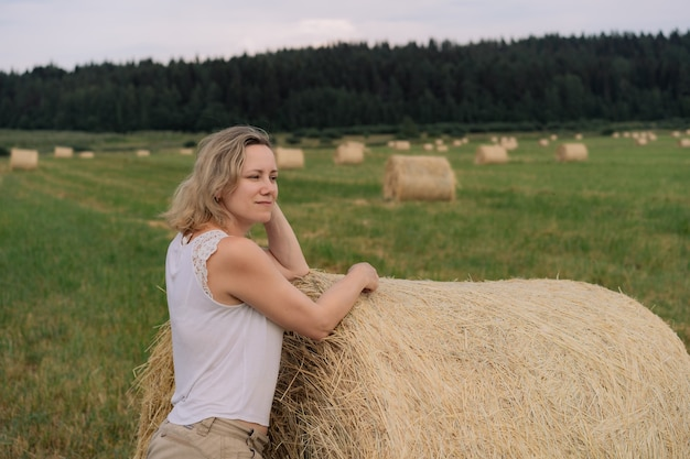 Młoda piękna dama o blond włosach opiera się na stogu siana, patrząc na bok, stojąc w letnim polu