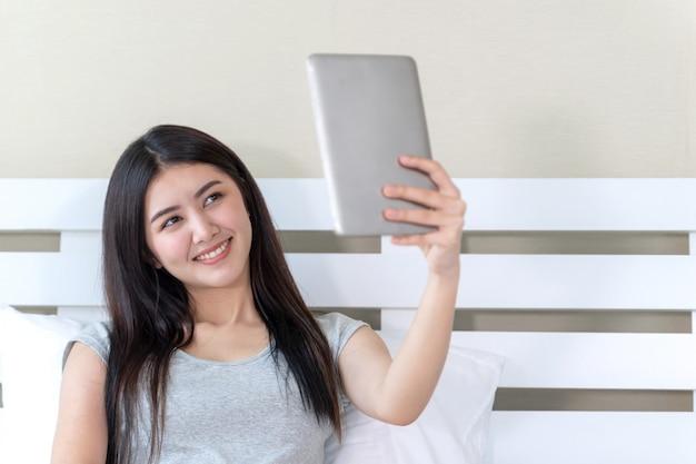 Młoda piękna dama sama biorąc zdjęcie, ona uśmiecha się ze szczęścia i selfie przez duży smartfon na łóżku w domu