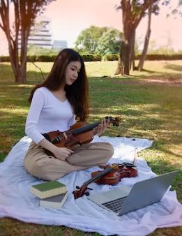 Młoda piękna dama trzyma w ręku skrzypce, patrząc na laptopa, ucząc się grać na instrumencie akustycznym.
