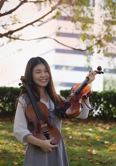 Młoda piękna dama trzyma w ręku skrzypce, z uczuciem radości, pozuje model, w parku, rozmyte światło wokół