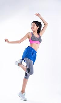 Młoda piękna dama ubrana w odzież sportową, rozstawiona na nogach, podnosząca ręce nad głowę, opadająca na jedno kolano, rozciągająca ciało przed ćwiczeniami, z radością