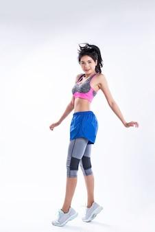 Młoda piękna dama ubrana w odzież sportową, stojąc rozstawionymi nogami, podnieś ręce do góry, skieruj palce w dół, potańcz do ćwiczeń z radością