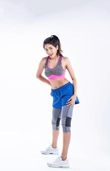 Młoda piękna dama ubrana w odzież sportową, stojąc w oddaleniu, podnosząc ręce, dotykając nogi, mały uśmiech, portret pozowanie, z radością