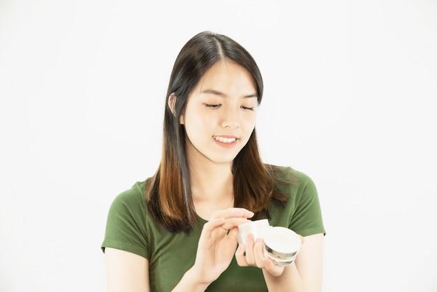 Młoda piękna dama używa moisturizer śmietankę dla twarzy skóry opieki - kobiety i kosmetyka makeup twarzy piękna skóry opieki pojęcie