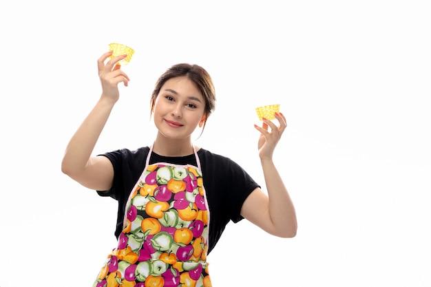 Młoda piękna dama w widoku z przodu w czarnej koszuli i kolorowej pelerynie, trzymająca żółte małe patelnie