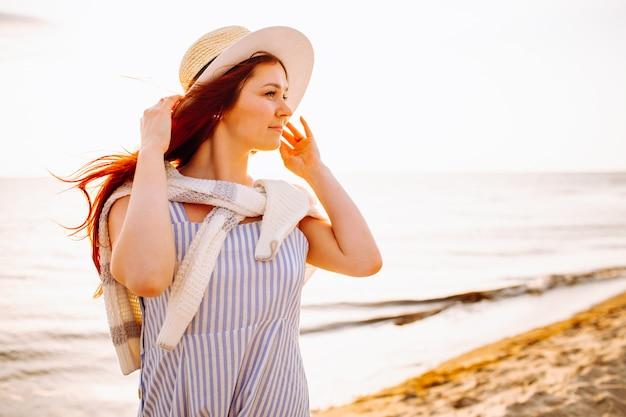 Młoda piękna długa z włosami kobieta w kapeluszu ono uśmiecha się przy plażą morze lub ocean przy zmierzchem. spokojny wieczór, romans.