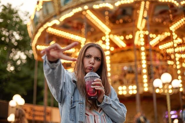 Młoda piękna długowłosa kobieta krzywi się podczas picia lemoniady, patrzy i marszczy brwi, stoi nad karuzelą z uniesionymi palcami w geście zwycięstwa