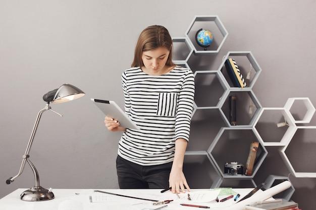 Młoda piękna, dobrze wyglądająca ciemnowłosa dziewczyna w pasiastej koszuli stojąca przy stole w wygodnym miejscu pracy w domu, trzymająca w rękach cyfrowy tablet, patrząca na dokumenty ze skoncentrowanym wyrazem twarzy, próbująca