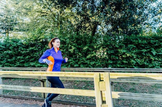 Młoda piękna dorosła kobieta biegająca przez park wiosną lub latem punkt koncepcja sport higiena osobista z włosami na wietrze