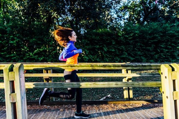 Młoda piękna dorosła kobieta biegająca przez park wiosną lub latem punkt sportowa koncepcja higieny osobistej z włosami na wietrze