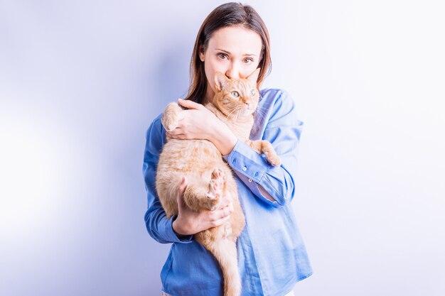 Młoda piękna dorosła kobieta trzyma jej kota na białym tle. koncepcja miłości do domowego zwierzaka