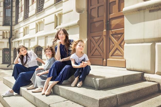 Młoda piękna dorosła mama i jej mała wesoła i córeczki spacerują razem po ulicach miasta