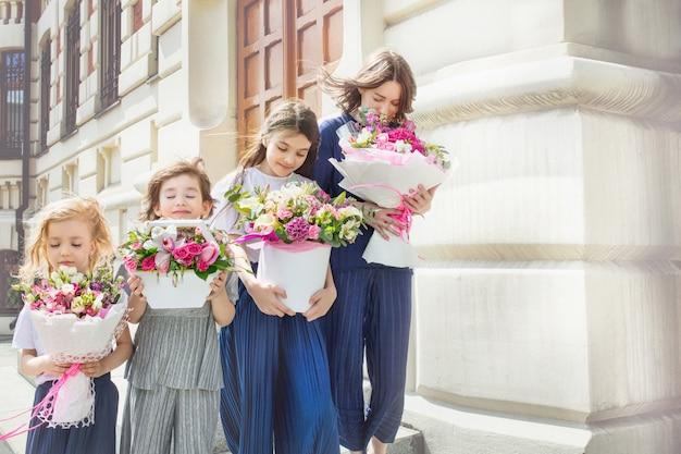 Młoda piękna dorosła mama i jej małe wesołe i szczęśliwe córki z bukietami kwiatów