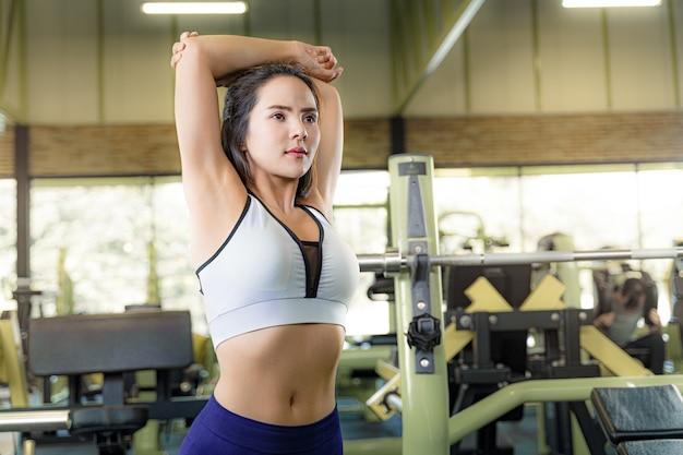 Młoda piękna dysponowana kobieta pracująca w gym out