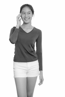 Młoda piękna dziewczyna azjatyckich nastolatka samodzielnie na białej ścianie w czerni i bieli