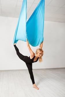 Młoda piękna dziewczyna ćwiczy powietrzny joga w gym.