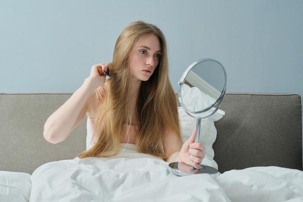 Młoda piękna dziewczyna czesanie długie włosy z pędzelkiem i lustrem