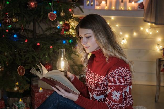 Młoda piękna dziewczyna czytając książkę w pobliżu choinki. portret dziewczynki w noc bożego narodzenia.