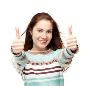 Młoda piękna dziewczyna daje dwa kciuki do góry