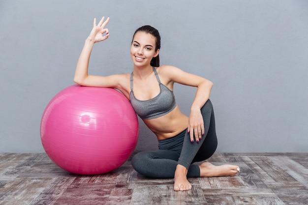 Młoda piękna dziewczyna fitness z różową piłką pokazując znak porządku na białym tle na szarym tle