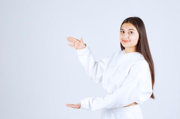 Młoda piękna dziewczyna gestykulując rękami pokazując znak duży i duży rozmiar.