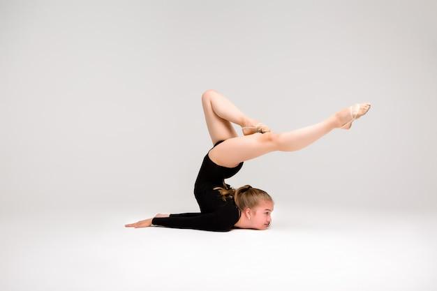 Młoda piękna dziewczyna gimnastyczka, młoda dziewczyna zajmuje się gimnastyką