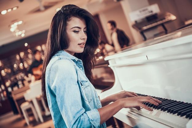 Młoda piękna dziewczyna gra na pianinie w sklepie muzycznym