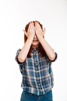 Młoda piękna dziewczyna imbir ukrywa oczy rękami na białej ścianie.