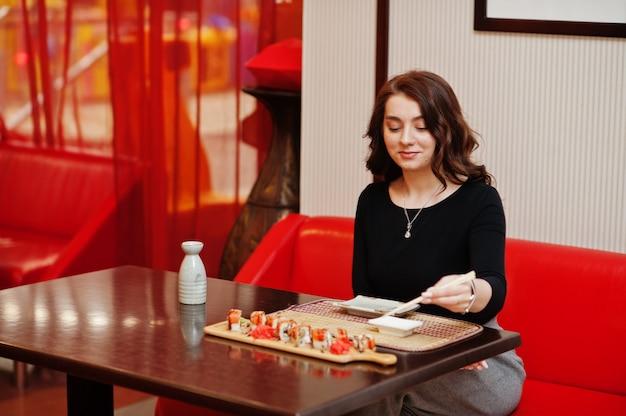 Młoda piękna dziewczyna je sushi w tradycyjnej japońskiej restauracji.
